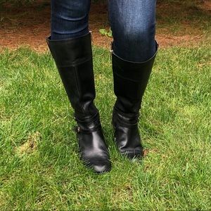 Black leather riding boots with gold buckles